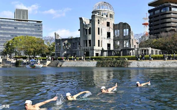 日本泳法を披露する参加者(1月中旬、広島市の元安川)=共同