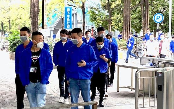 マスク姿で勤務するBYDの従業員(10日、広東省深圳市)