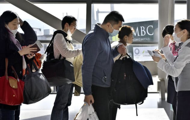 新興感染症を正しく恐れるのは難しい(マスク姿で上海行きの便に乗り込む利用客ら、関西空港)