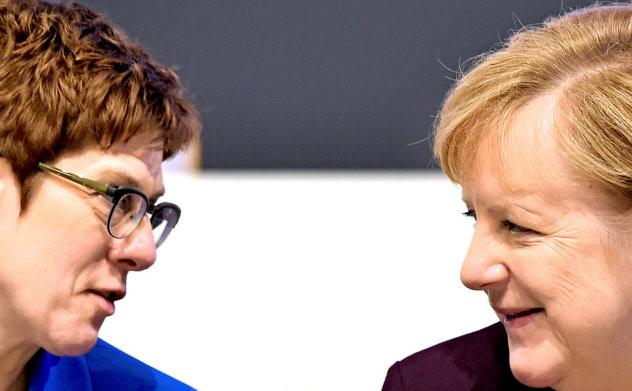 独与党CDU党首を退く意向を固めたクランプカレンバウアー氏(左)とメルケル首相=ロイター