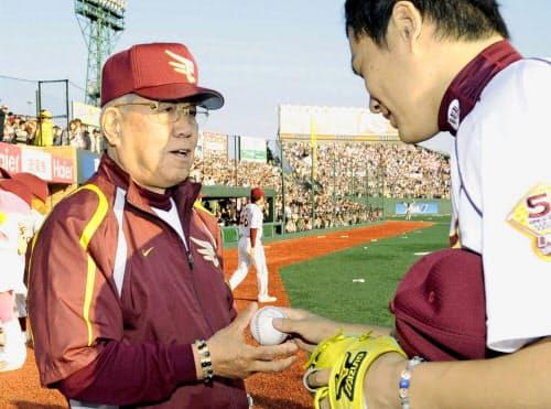 2009年4月、監督通算1500勝を達成し、田中将大投手(右)からウイニングボールを受け取る楽天・野村克也監督=共同