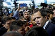 11日、ベネズエラに到着し、報道陣や政権支持者に囲まれるグアイド国会議長(11日、カラカス近郊)=ロイター