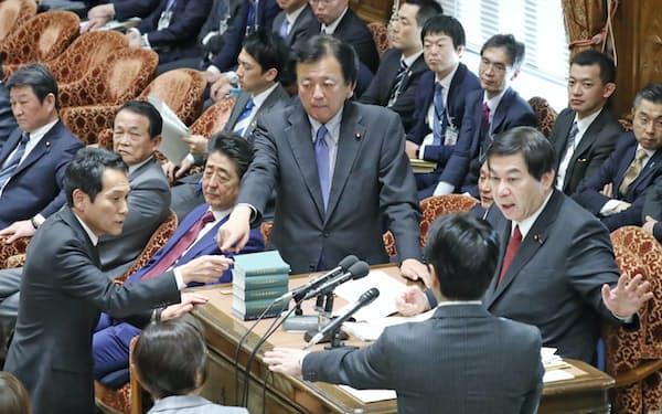 衆院予算委で閣僚席からのヤジに野党が強く反発、棚橋委員長(右端)に抗議する野党理事(12日)