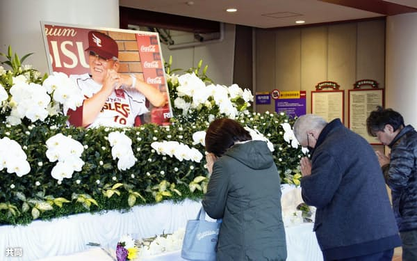 楽天生命パーク宮城に設置された野村克也元監督の献花台に手を合わせる人たち(12日午前、仙台市)=共同