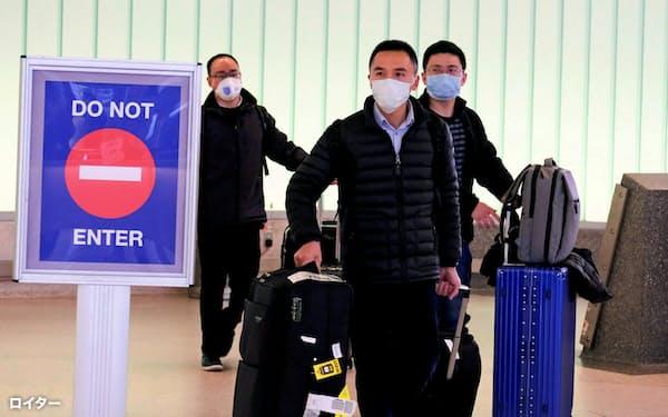 中国・上海から到着し、マスクをして降り立つ旅客(米ロサンゼルス空港)=ロイター