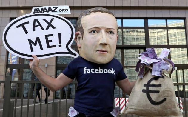 EU本部前でフェイスブックのザッカーバーグCEOにふんしてデジタル課税を訴える人物=ロイター