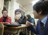 自主夜間中学で、高齢の生徒らに話しかける城之内庸仁さん(右、岡山市)=共同