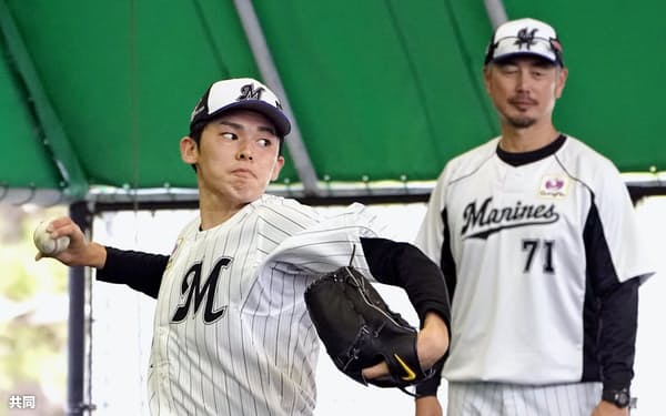 初のブルペンで投球練習する佐々木朗。右は吉井コーチ=共同