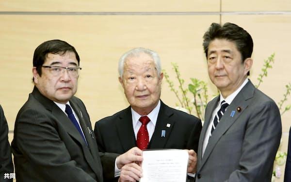 安倍首相(右)と面会した拉致被害者家族会の飯塚繁雄代表(中央)=14日午後、首相官邸