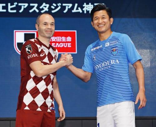Jリーグ開幕を前に開かれたキックオフカンファレンスで、握手を交わす神戸・イニエスタ(左)と横浜FC・三浦(14日、東京都内)=共同