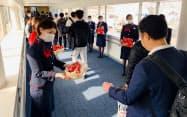 マスク姿の女性の客室乗務員らが箱に入れてチョコレートを配った(14日、羽田空港)