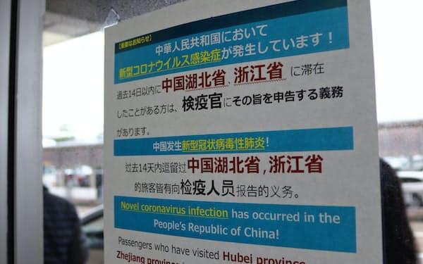 小松空港の国際線ターミナルの入り口には、新型コロナウイルスについて注意喚起するポスターが貼られている(14日、石川県小松市)