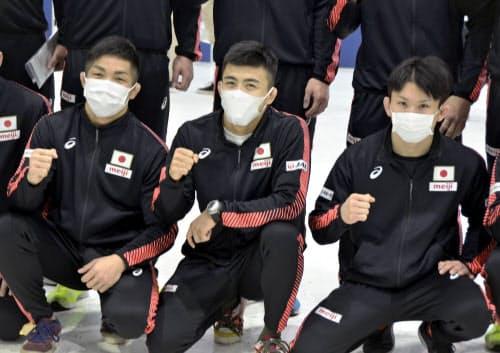 アジア選手権出発を前に、マスク姿で写真撮影に応じるレスリング東京五輪代表の文田健一郎(中央)ら(15日午前、成田空港)=共同