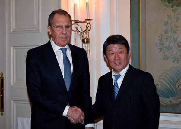 握手する茂木外相(右)とラブロフ外相(15日、ミュンヘン)=外務省提供