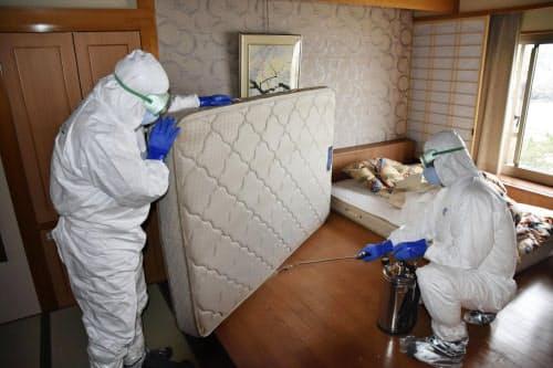客室で消毒液を吹きかける防護服姿の作業員(16日午後、千葉県勝浦市の「勝浦ホテル三日月」)=共同