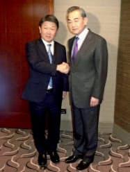 握手する茂木外相(左)と中国の王毅国務委員兼外相(15日、ドイツ・ミュンヘン)=共同