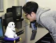 デモンストレーションでロボットと会話をする男性(1月27日、長崎大)=共同