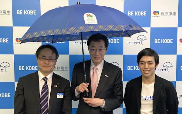 傘は神戸の街をイメージした青いタータン柄(17日、神戸市の久元喜造市長(中)ら)