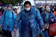 感染防止のためマスクとレインコートをつけて歩く人たち(17日、上海市)=ロイター
