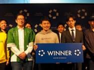 スタートアップ・カタパルトで優勝したアダコテックの河邑亮太取締役(写真中央、18日、福岡市内)