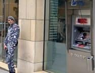 破壊された銀行ATMの前に立つレバノンの兵士(17日、ベイルート)