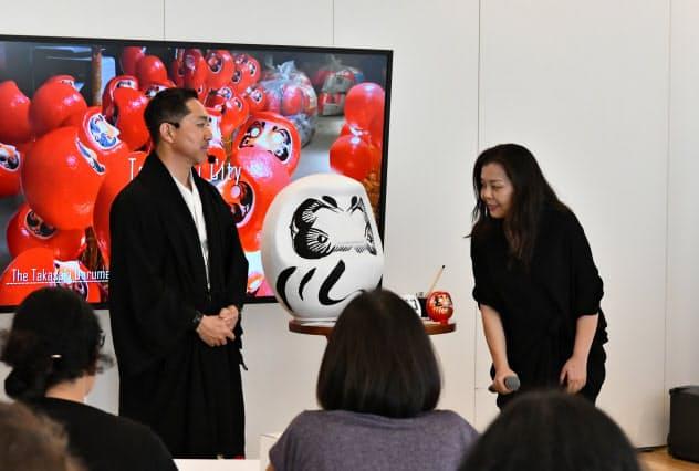 高崎だるまについて解説する今井だるま店NAYAの今井裕久社長(左)(18日、サンパウロ)