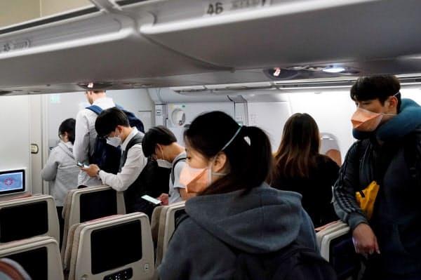 韓国の仁川国際空港に着陸した機内でマスクをつける乗客=ロイター