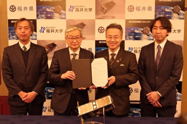 超小型衛星の開発で覚書を締結した福井県の杉本達治知事(中央右)と福井大の上田孝典学長(中央左)=福井市内