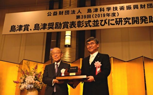 腰原教授(右)は光で物質の性質が変化する現象を発見した(京都市)