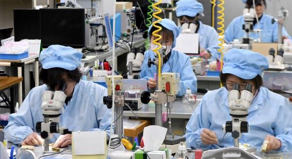 顕微鏡をのぞき込みながら、小さいもので太さ1ミリに満たない部品を組み立てる(秋田県鹿角市の川島製作所秋田工場)
