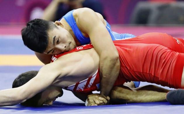 男子グレコローマン60キロ級準決勝 ウズベキスタン選手を攻める文田健一郎(19日、ニューデリー)=共同