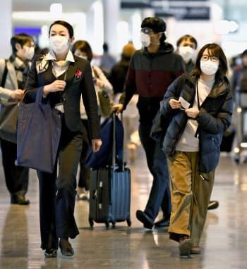 成田空港でマスクをして歩く人たち(2月18日)=共同