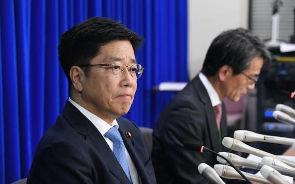 記者会見する加藤厚労相(左)(19日、厚労省)