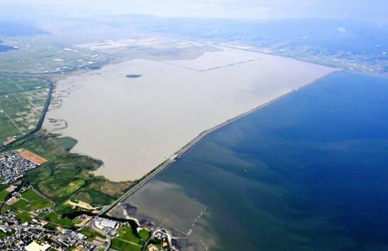 国営諫早湾干拓事業の潮受け堤防によって閉め切られた調整池。右は有明海(2019年9月、長崎県諫早市)=共同
