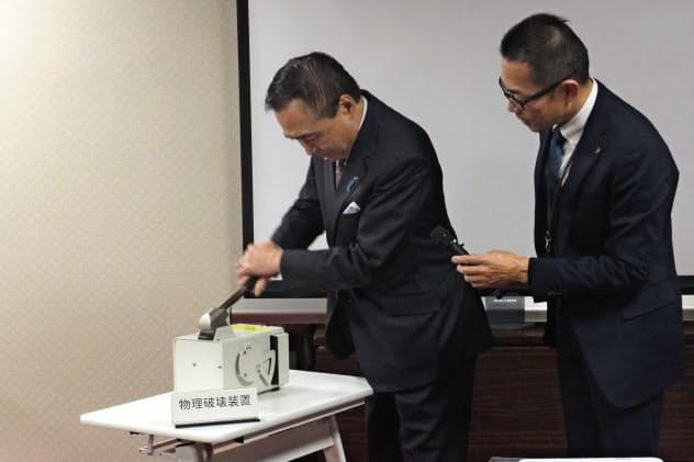 手動でHDDに穴をあける処理をする黒岩知事(神奈川県庁)