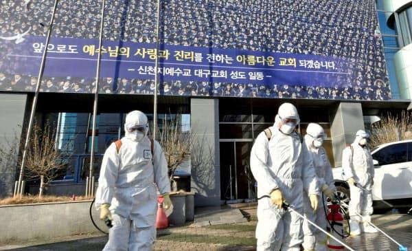 新興宗教団体の教会前を消毒する防疫当局者(19日、韓国・大邱)=聯合・ロイター