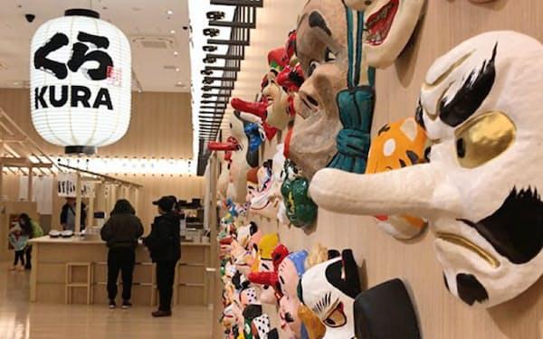 様々なお面を壁に掲げたくら寿司の店舗(東京・浅草)