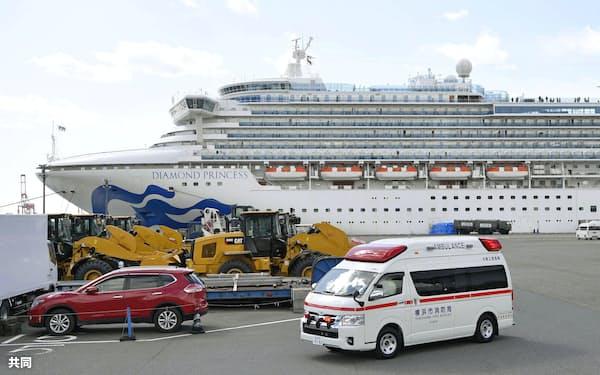 クルーズ船「ダイヤモンド・プリンセス」が停泊する横浜港から出る救急車(18日)=共同