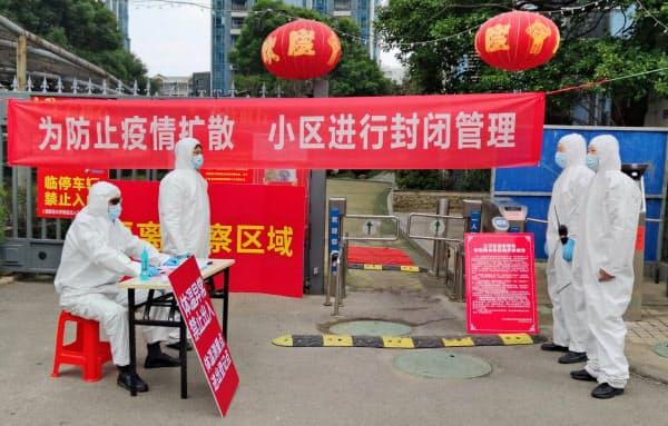 湖北省武漢市の住宅入り口で検温などをする作業者(13日)=ロイター