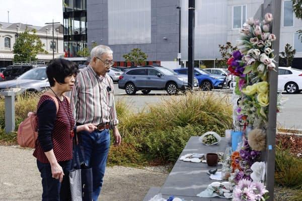 20日、ニュージーランド・クライストチャーチで、カンタベリーテレビビルの跡地を訪れた堀田和夫さん(右)と聖子さん=共同