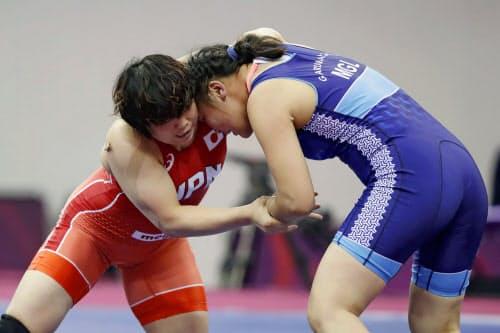 女子76キロ級準決勝 モンゴル選手(右)と対戦する皆川博恵(20日、ニューデリー)=共同
