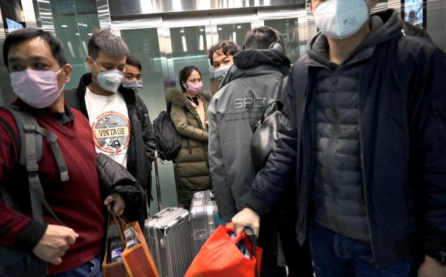 マスク姿でエレベーターに乗る人たち(20日、北京大興国際空港)=ロイター