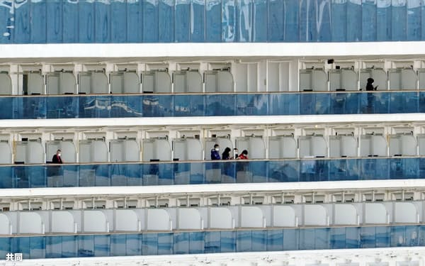 横浜港に停泊中のクルーズ船「ダイヤモンド・プリンセス」のベランダで過ごす乗客(20日)=共同