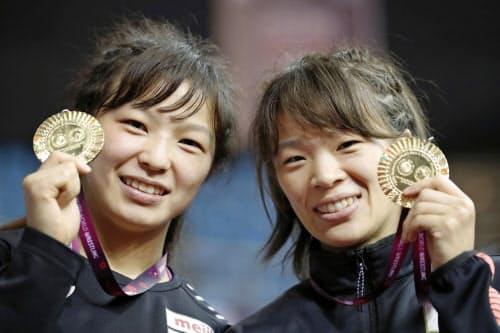 姉妹で優勝し、笑顔を見せる57キロ級の川井梨紗子(右)と62キロ級の友香子(21日、ニューデリー)=共同