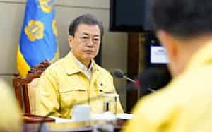 新型コロナウイルスの感染状況について報告を受ける文大統領(21日)=韓国大統領府提供