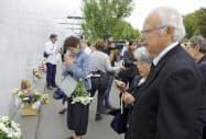 ニュージーランド地震の追悼式典で献花する(手前右から)鈴木陽子さんの父喜久男さんと母千鶴子さん(22日、クライストチャーチ)=共同