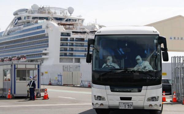 クルーズ船「ダイヤモンド・プリンセス」(奥)を後にするバス。運転手は防護服に身を包んでいた(22日午前、横浜港)=共同
