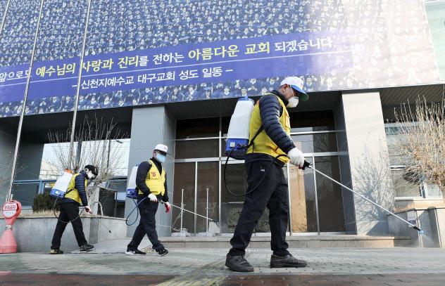 新型コロナウイルスの感染が相次いで発生した韓国・大邱の教会周辺を消毒する保健所の関係者(20日)=聯合・共同