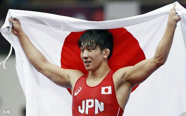 男子フリー65キロ級で優勝し、日の丸を掲げる乙黒拓斗(22日、ニューデリー)=共同