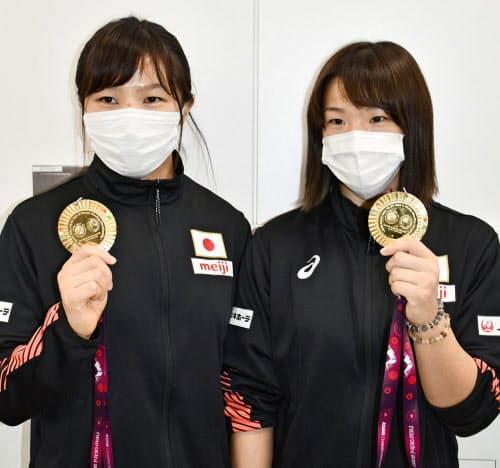 帰国し、金メダルを手に取材に応じるレスリングの川井梨紗子(右)と妹の友香子(23日、成田空港)=共同